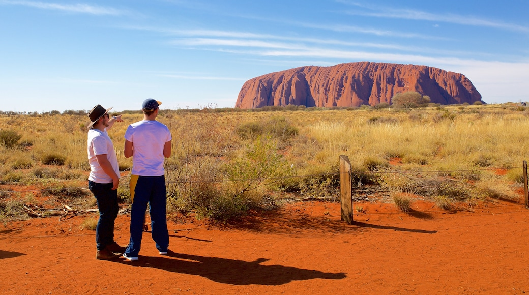 Uluru which includes landscape views and desert views as well as a couple