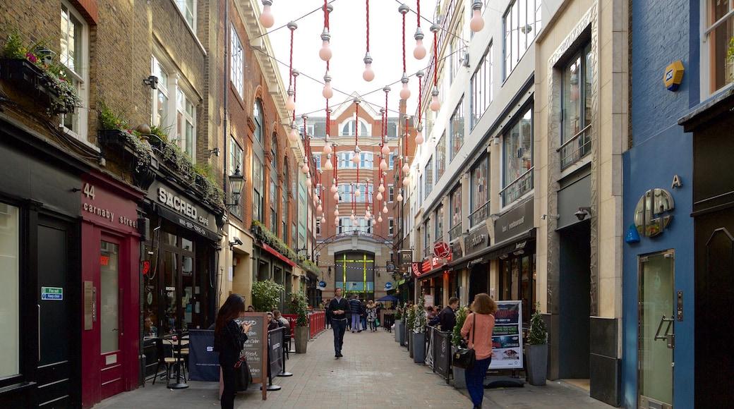 Carnaby Street caracterizando arquitetura de patrimônio e uma praça ou plaza assim como um pequeno grupo de pessoas
