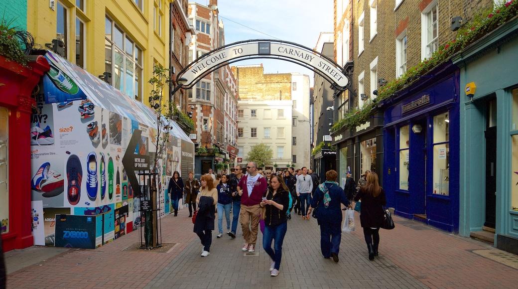 Carnaby Street som inkluderar ett torg och historisk arkitektur såväl som en stor grupp av människor