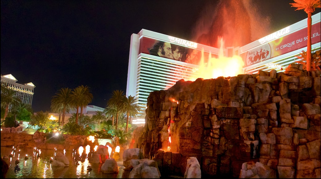 Mirage Volcano showing a casino, night scenes and a pond