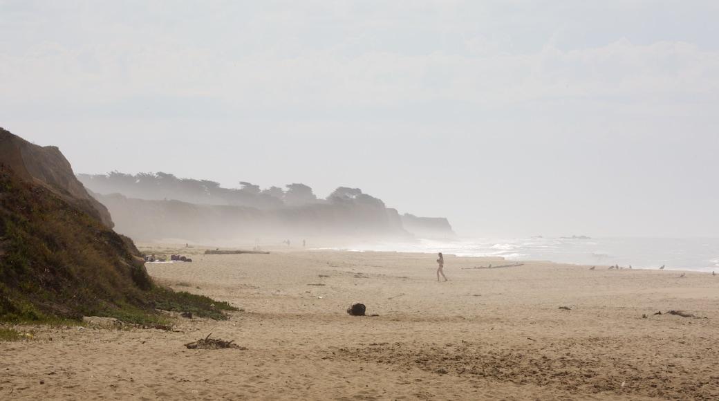 Half Moon Bay das einen Strand und allgemeine Küstenansicht sowie einzelne Frau