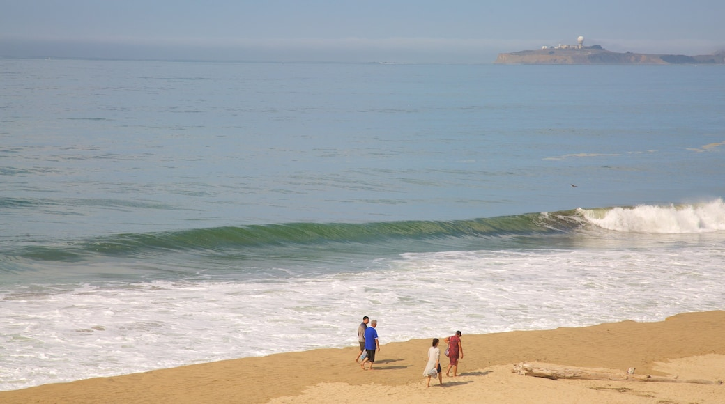 Half Moon Bay showing general coastal views and a sandy beach as well as a small group of people