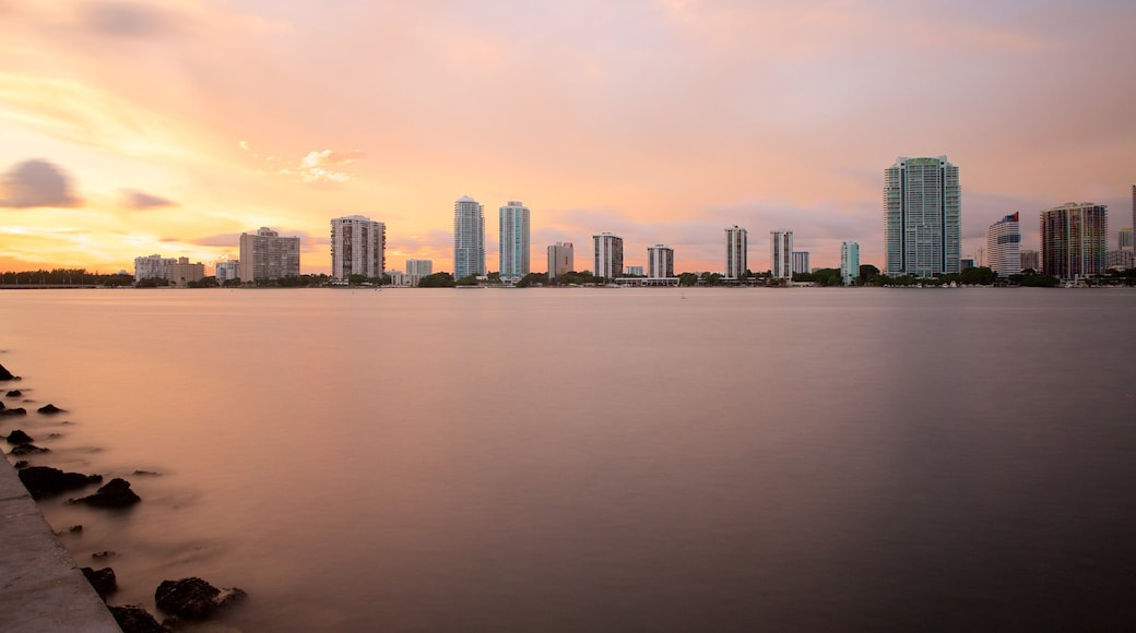 Miami which includes skyline, a lake or waterhole and a sunset