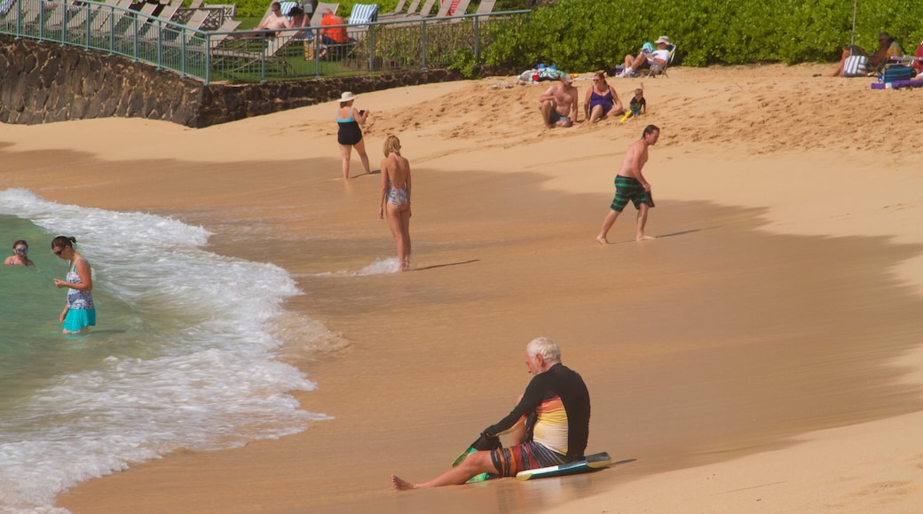 Poipu Beach which includes a sandy beach as well as a small group of people