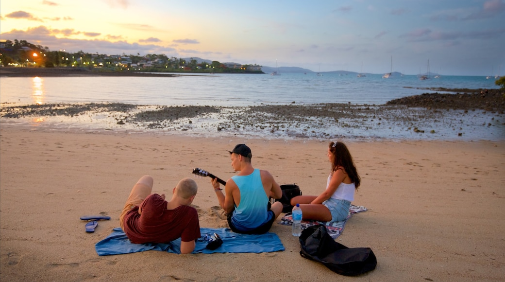 Airlie Beach showing a sandy beach and a sunset as well as a small group of people