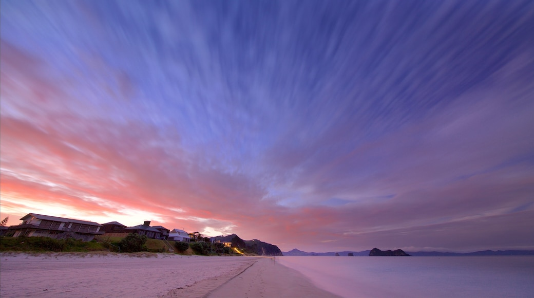 Hahei Beach which includes a sandy beach, a bay or harbour and a sunset