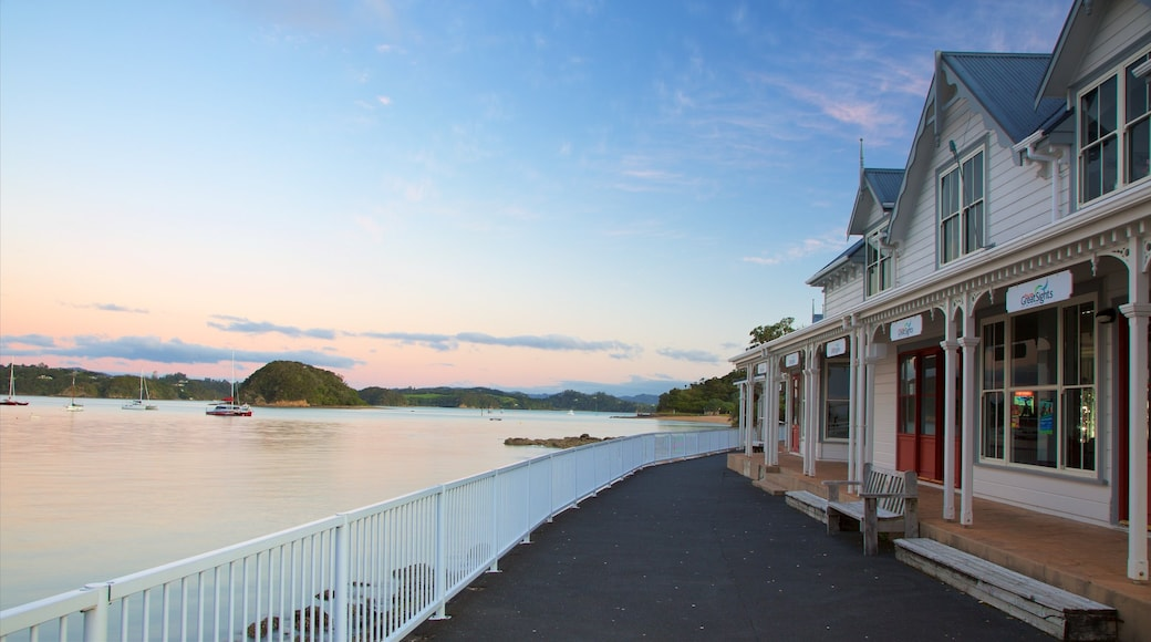 Paihia Wharf which includes a coastal town, a bay or harbour and a sunset