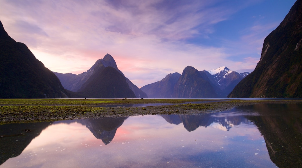 Milford Sound featuring a lake or waterhole, a sunset and mountains