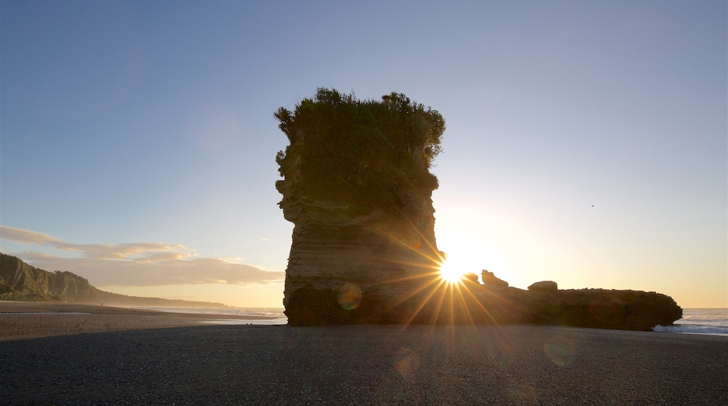 Punakaiki which includes a beach, rocky coastline and a sunset