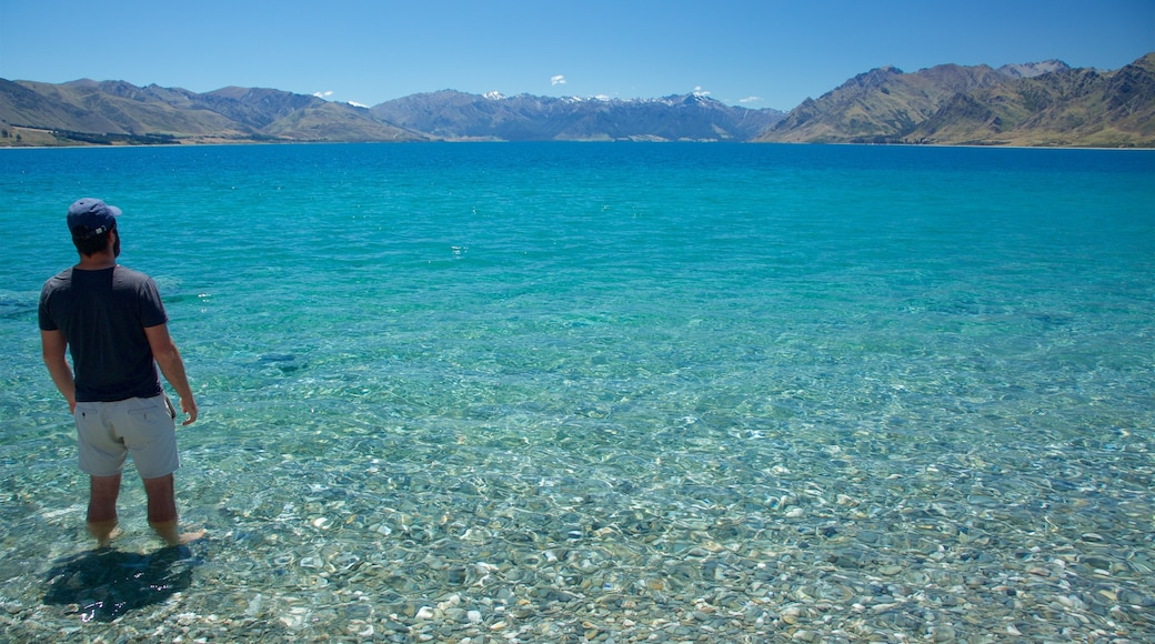 Lake Hawea which includes a lake or waterhole, mountains and a pebble beach