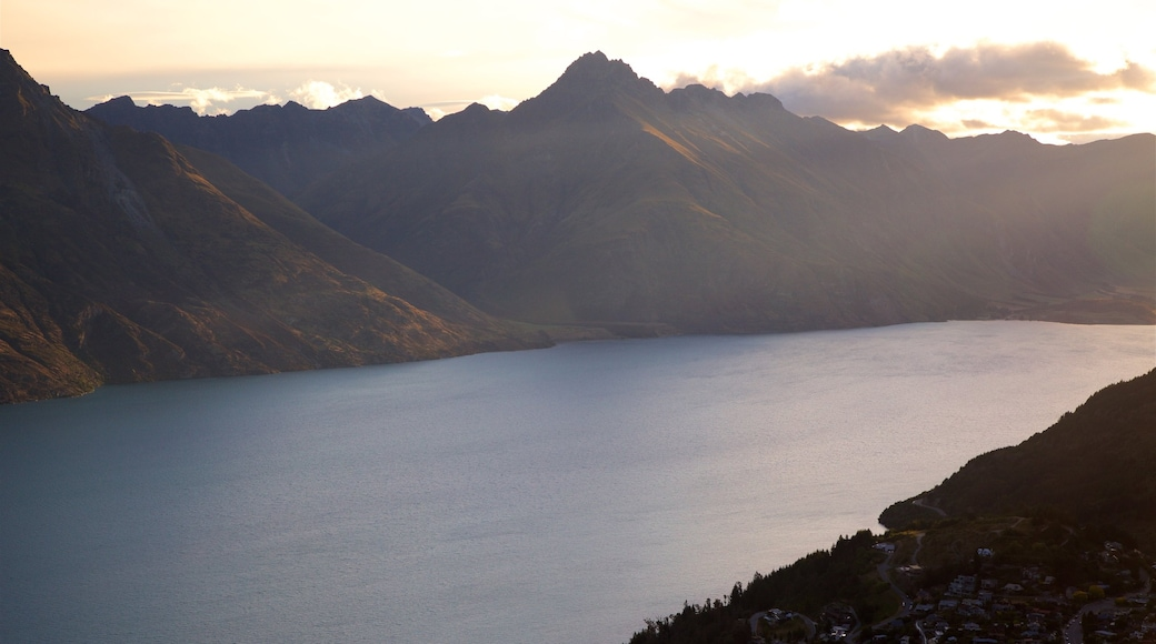 Sunshine Bay which includes a lake or waterhole, a sunset and mountains