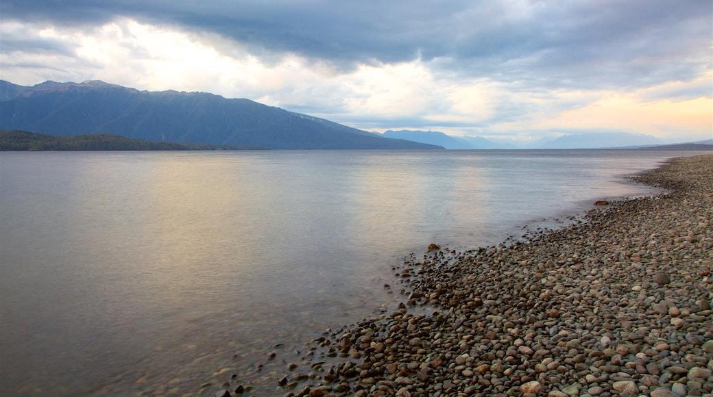 Lake Te Anau featuring a sunset, a pebble beach and mountains
