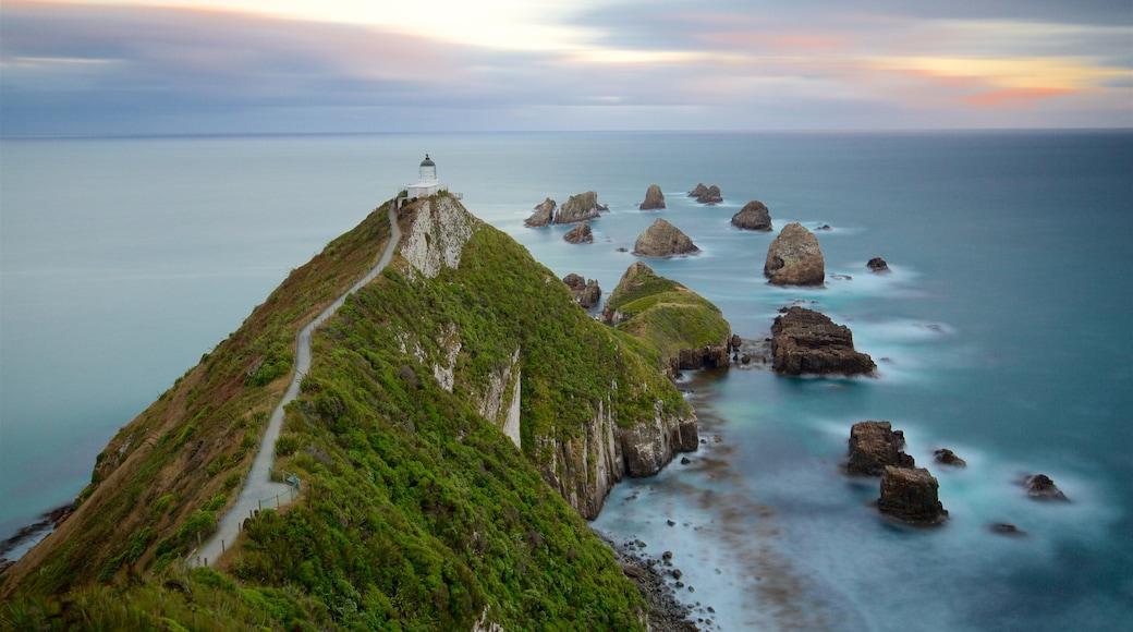 Nugget Point Lighthouse which includes rocky coastline, mist or fog and a lighthouse
