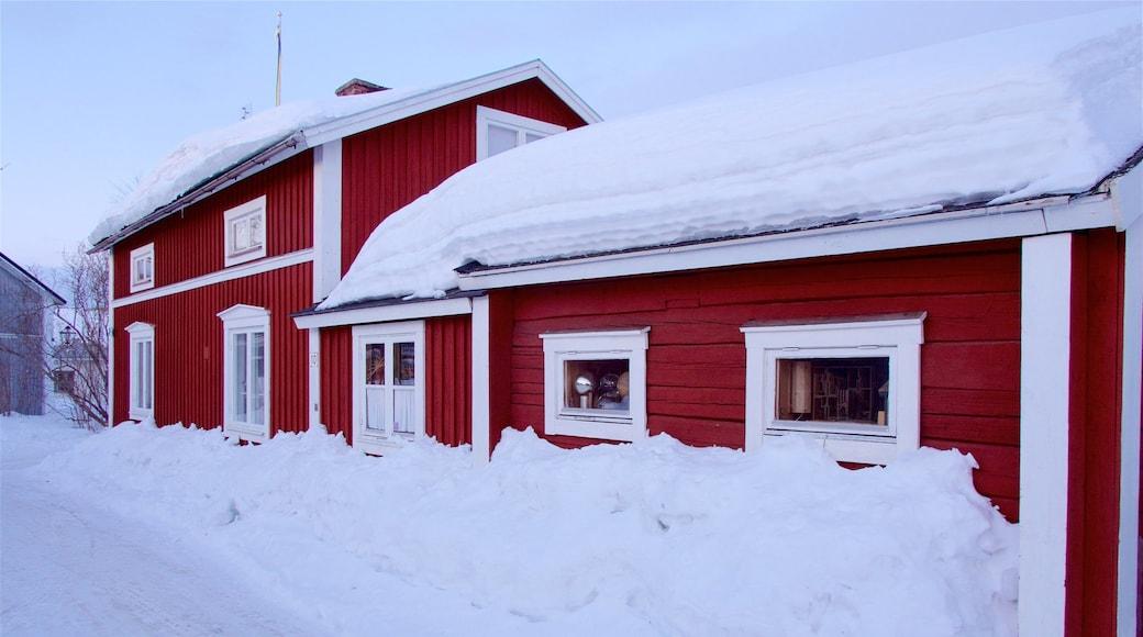 Gammelstads kyrka som inkluderar snö och ett hus
