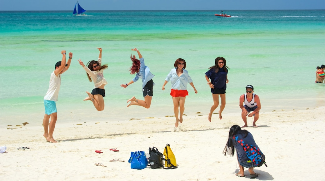Boracay Island which includes a sandy beach and tropical scenes as well as a small group of people