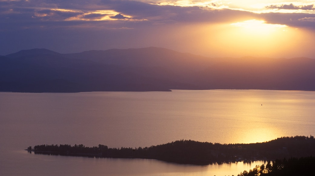 Flathead Lake which includes a lake or waterhole and a sunset