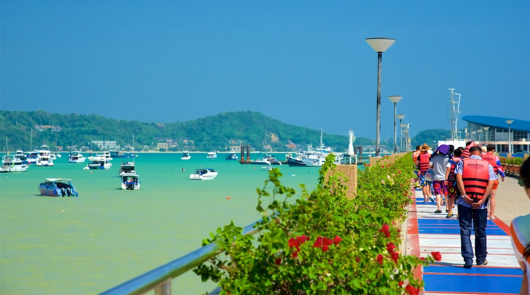Chalong Pier which includes a bay or harbour and boating as well as a small group of people