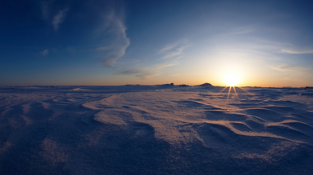 Nome which includes a sunset and snow