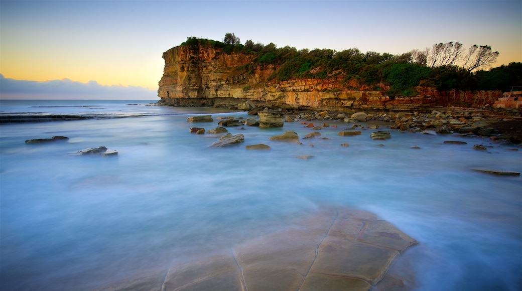 Terrigal featuring rocky coastline, a bay or harbour and a sunset