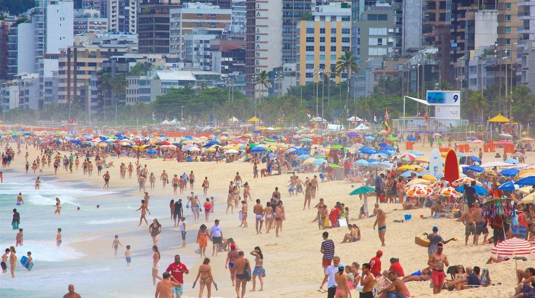 Playa de Ipanema que incluye una playa de arena y una ciudad costera y también un gran grupo de personas