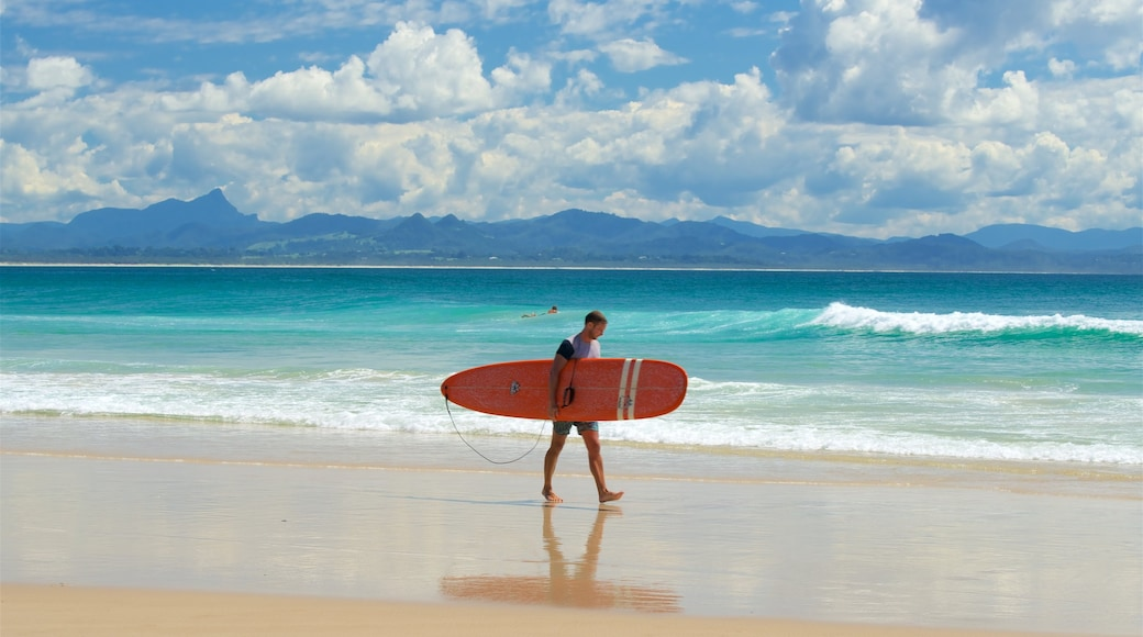 Wategos Beach featuring a sandy beach and surfing as well as an individual male