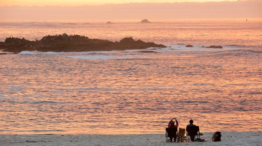 17-Mile Drive que inclui uma praia de areia e um pôr do sol assim como um casal