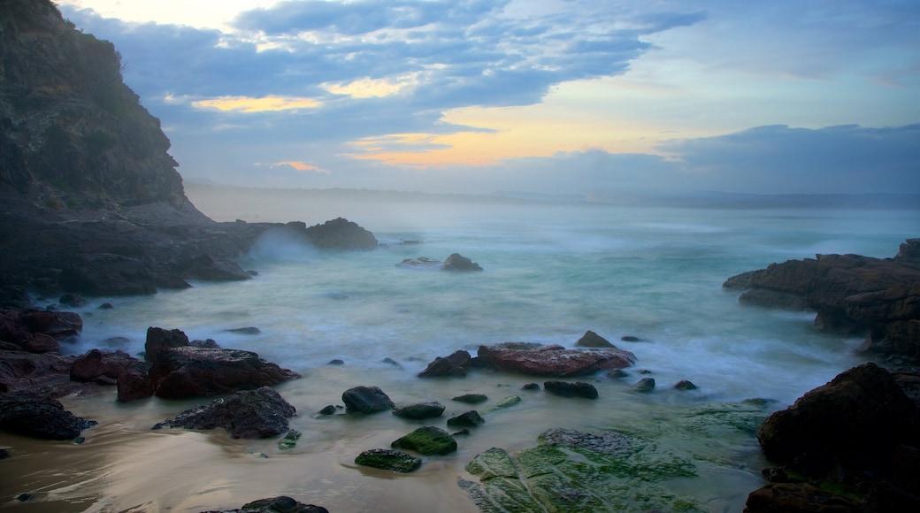 Pambula Beach featuring rocky coastline, a sandy beach and a sunset
