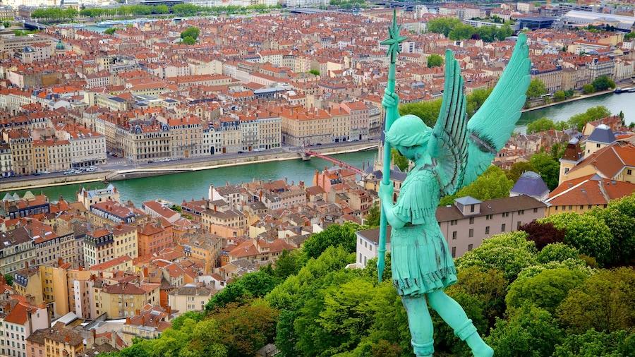 Lione mostrando fiume o ruscello, statua o scultura e città