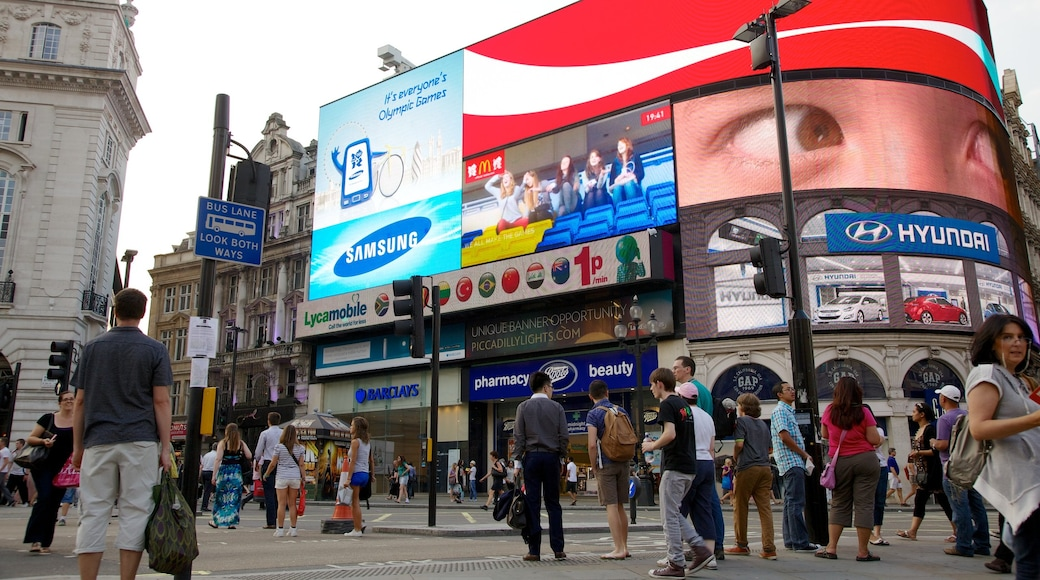 Piccadilly Circus showing a city and signage as well as a large group of people