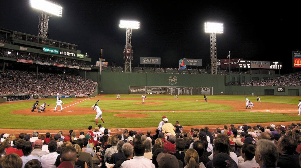 Fenway Park showing night scenes and a sporting event as well as a large group of people