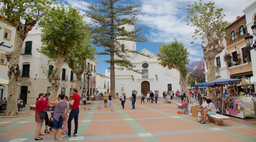 Nerja showing a small town or village and a square or plaza as well as a large group of people