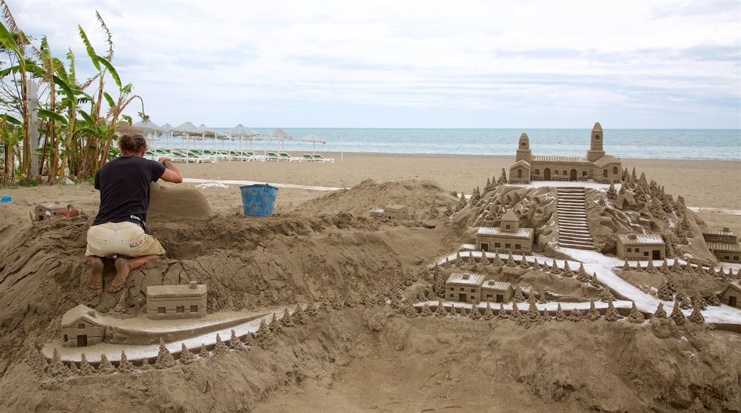 Torremolinos showing a beach and outdoor art as well as an individual male