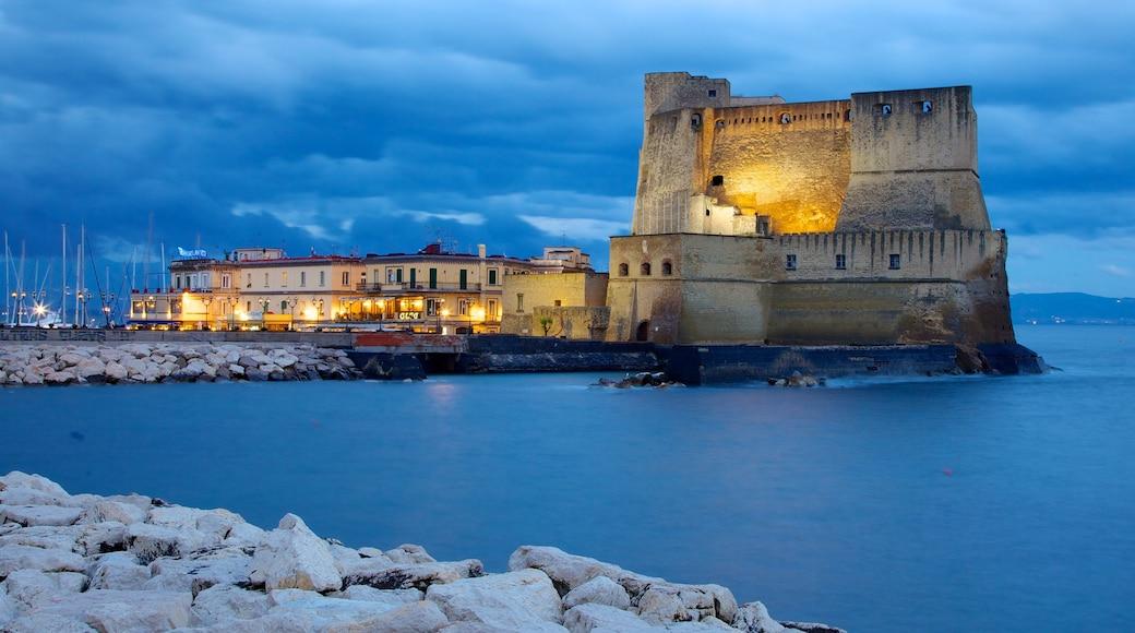Castel dell\'Ovo que incluye arquitectura patrimonial, vistas de una costa y escenas nocturnas