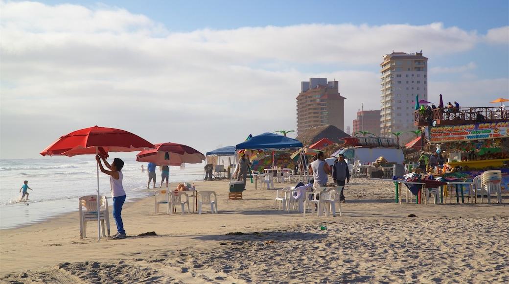 Rosarito que incluye vistas generales de la costa y una playa de arena y también un pequeño grupo de personas