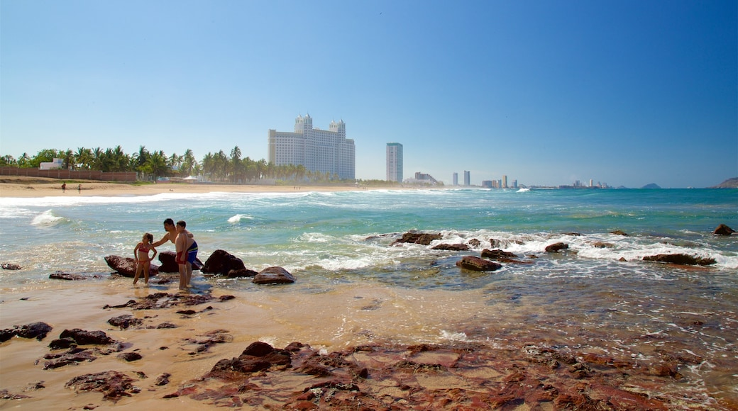 Mazatlan featuring rugged coastline and a sandy beach as well as a family