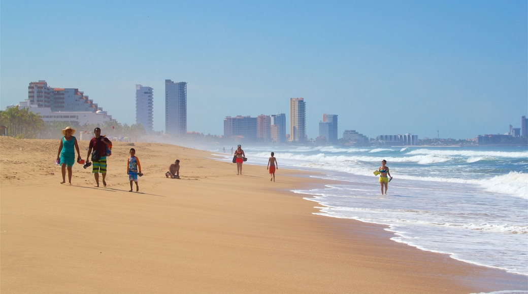 Mazatlán mostrando una playa y olas y también una familia