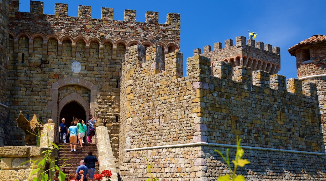 Castello di Amorosa featuring heritage elements and chateau or palace as well as a small group of people
