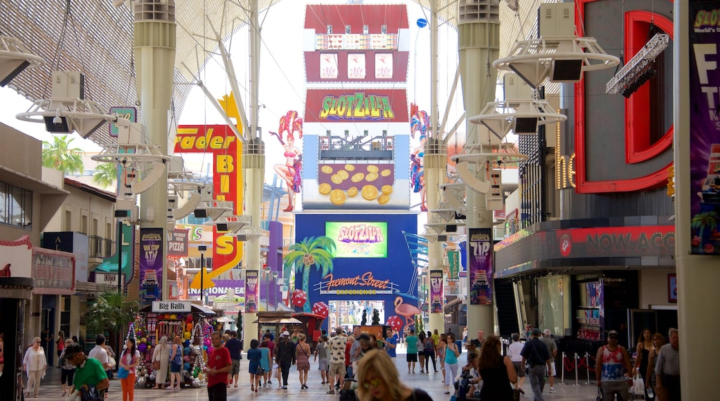 Downtown Las Vegas featuring signage as well as a small group of people