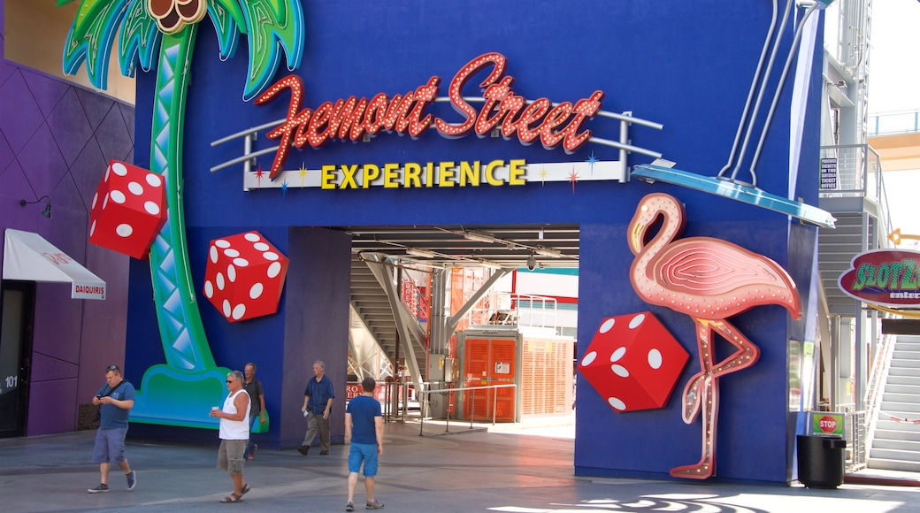 Downtown Las Vegas showing signage as well as a small group of people