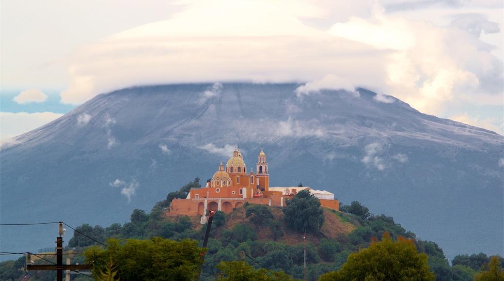 La Virgen de los Remedios Sanctuary showing mist or fog, heritage elements and mountains
