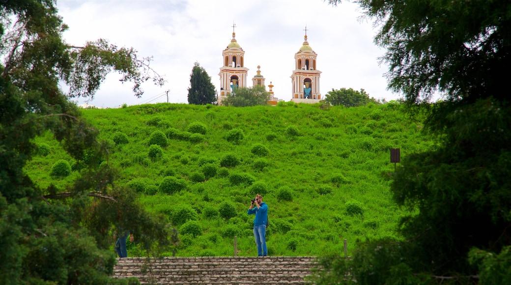 Gran Pirámide de Cholula ofreciendo escenas tranquilas y una iglesia o catedral y también un hombre
