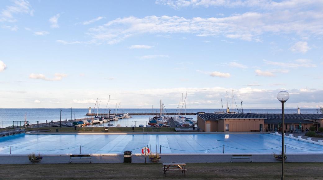 Hjo som inkluderar kustutsikter, en pool och en hamn eller havsbukt