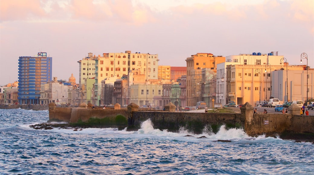 Malecón showing a city, a sunset and a bay or harbour