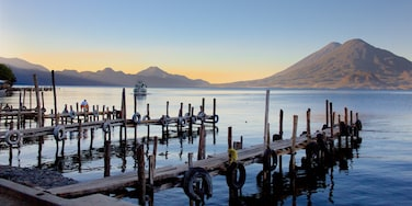Guatemala showing a sunset, a lake or waterhole and mountains