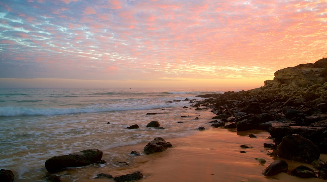 Falesia Beach featuring a beach, a sunset and rocky coastline