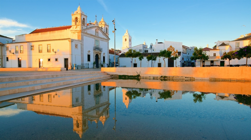 Lagos which includes a church or cathedral, a lake or waterhole and a sunset