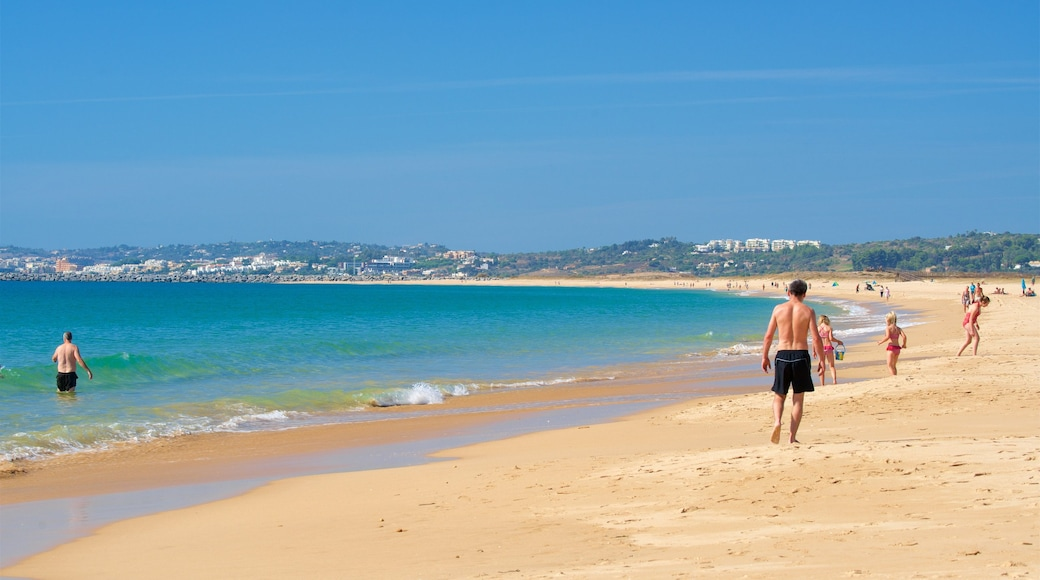 Alvor Beach featuring general coastal views and a sandy beach as well as a small group of people