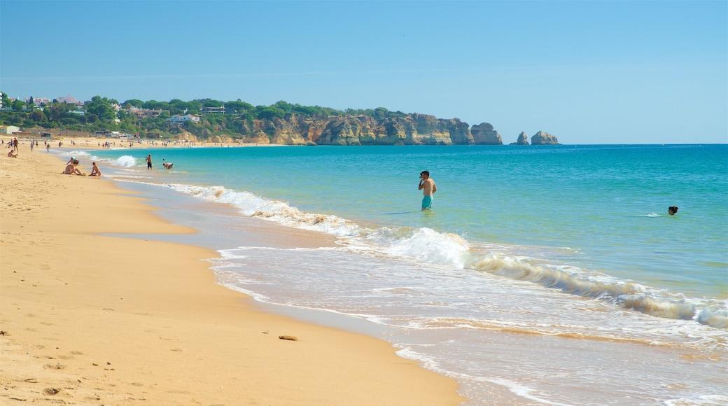 Alvor Beach featuring a sandy beach, general coastal views and swimming