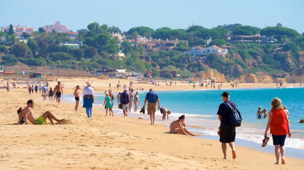 Alvor Beach showing general coastal views and a sandy beach as well as a small group of people