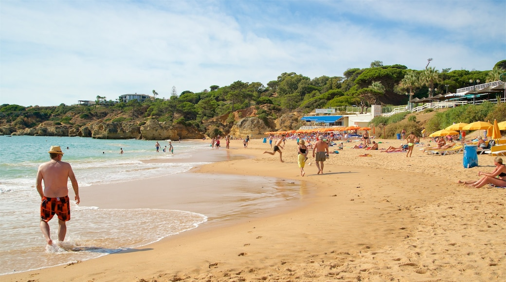 Oura Beach which includes general coastal views and a sandy beach as well as a small group of people